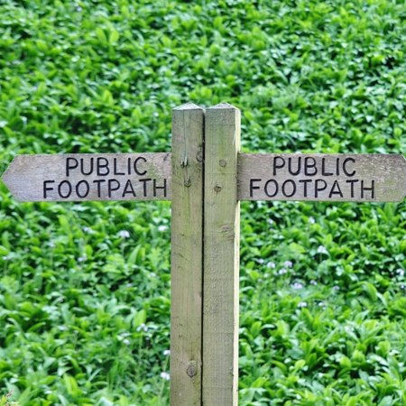 Traditional public footpath signs in green fields on our Cotswold walking trip