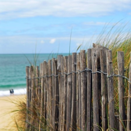 Fenced sand dune leading to a beach and open sea on our French cycling holiday