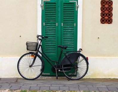 Black bicycle leant against a green door - our favourite bike blogs