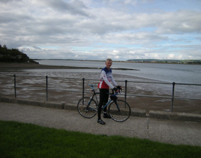 Photo of the host for our cycling holidays and walking tours of Devon and Cornwall, Ian - pictured here on his bicycle on a road beside the sea