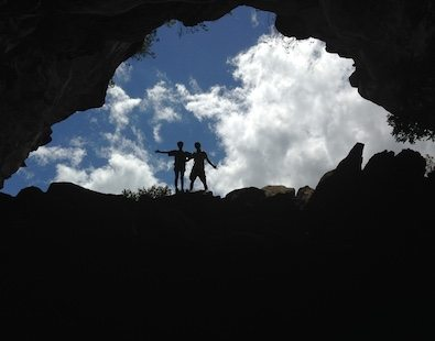 Walking holiday photo of two of the Carter Company team, taken from a cave and silhouetted against a blue sky