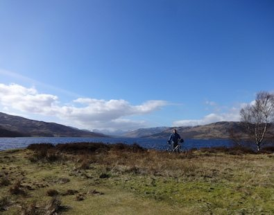 One of The Carter Company team members standing with his bike, with Loch Katrine and mountains in the background