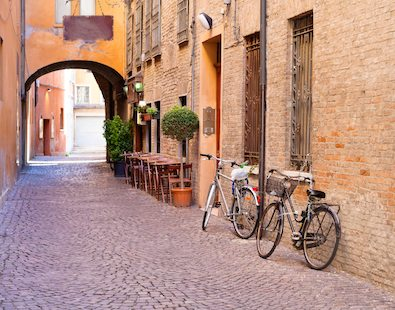 Two bikes resting against the wall on an old French street on our Provence cycling holiday