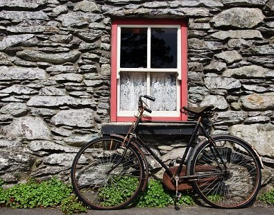 Old bike leaning against stone wall house seen on our Connemara, Ireland cycling holiday