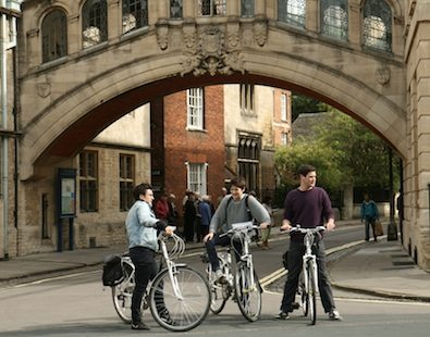Three cyclists on a bike holiday in Oxford, pausing under the Bridge of Sighs