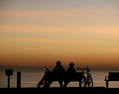 Cyclists rest on a bench and enjoy a beautiful sunset